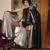 Frank-N-Furter, from The Rocky Horror Picture Show. Boned Corset, Silver Lame Lined Satin Cape with Over Sized Collar, Lace Gater Belt, Over Sized Pearl Necklace and Fingerless Gauntlets (gloves).